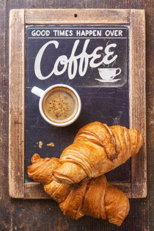 Coffee cup and croissants on vintage slate chalk board